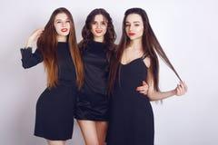 Galen partitid av tre härliga stilfulla kvinnor i tillfällig svart klänning för elegant afton som firar och att ha gyckel som dan Arkivbild