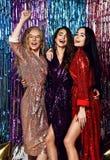 Galen partitid av tre h?rliga stilfulla kvinnor i elegant dr?kt som firar nytt ?r, f?delsedag och att ha gyckel, dans royaltyfri bild