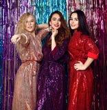 Galen partitid av tre h?rliga stilfulla kvinnor i elegant dr?kt som firar nytt ?r, f?delsedag och att ha gyckel, dans royaltyfri foto