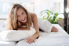 Galen skratta flicka som lokaliserar på sängkläder royaltyfria bilder