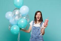 Galen skrikig ung kvinna som blinkar och att rymma den plast- koppen av cola eller sodavatten som firar med färgrika luftballonge arkivfoto