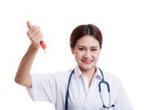 Galen ung asiatisk kvinnlig doktorshåll en injektionsspruta Fotografering för Bildbyråer
