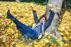 Galen ung kvinna som kastar gulingsidor i hösten, säsongsbetonad lif royaltyfria foton