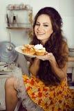 Galen verklig hemmafru på kök som ler att äta Arkivfoton