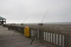 Galenskapstrand South Carolina, Februari 17, 2018 - två fiskepoler som lutar mot en träräcke på galenskap, sätter på land fiskepi Arkivfoto