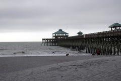 Galenskapstrand South Carolina, Februari 17, 2018 - vågor som rullar upp stranden bredvid strandpromenad på och mulen dag Royaltyfri Bild