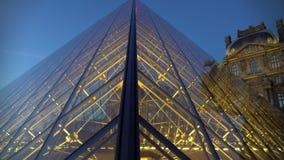 A galeria do museu de arte vista através da parte externa de vidro da pirâmide iluminou o palácio do Louvre filme