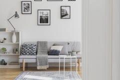 Galerij van zwart-witte foto's boven grijze bank met hoofdkussens en deken royalty-vrije stock fotografie