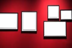 Galerijbinnenland met lege kaders op rode muur Stock Fotografie