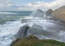Gales hit Mullion Cove, Cornwall. Gales hit Mullion Cove, and crash over the harbour walls, in the stunning county of Cornwall royalty free stock images
