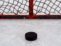 Galet d'hockey dans le réseau photographie stock libre de droits