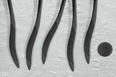 Galet d'hockey et cinq bâtons Photo stock