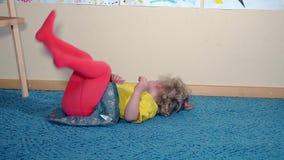 Galet flickabarn som hemma spelar på golv arkivfilmer