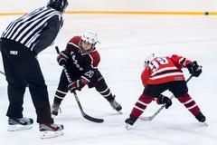 Galet jouant entre les joueurs des équipes de glace-hockey Image libre de droits