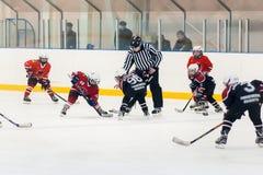Galet jouant entre les joueurs des équipes de glace-hockey Image stock