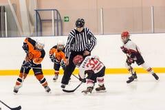 Galet jouant entre les joueurs des équipes de glace-hockey Photos stock