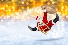 Galet Santa Claus flyg på hans backgro för bokeh för slädesnö guld- arkivfoto