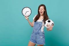 Galet skrikigt fotbollsfanjubel för ung kvinna upp det favorit- laget för service med fotbollbollen, rund klocka som isoleras på  royaltyfria foton