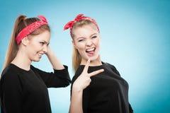 Galet stift upp retro flickor som gör roliga framsidor Arkivfoto