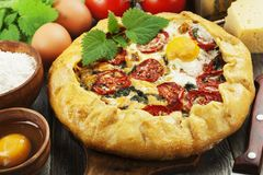 Galette with nettle. Tomatoes, cheese and egg royalty free stock image