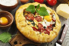 Galette with nettle. Tomatoes, cheese and egg stock image