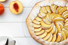Galette o empanada hecho en casa con las nectarinas en la tabla de madera blanca Imagen de archivo