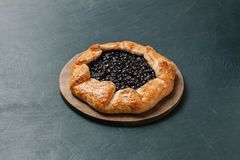 Galette with seasonal berries. Flat lay crispy summer berry pie on a gray-blue background royalty free stock photo