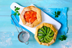 Galettes with fruits. Assorted open-faced simple rustic pies or galettes with fresh fruits Royalty Free Stock Photos