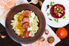 Galetti Pasta with pieces of sausage, yellow tomatoes and creamy mustard sauce in a clay bowl and beet salad Royalty Free Stock Images