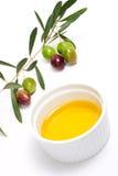 Galho das azeitonas e petróleo verde-oliva puro imagem de stock royalty free