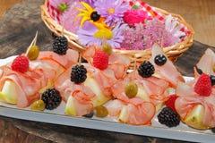 Galia melon, melon with ham, raspberries, blueberries, blackberr Stock Photos