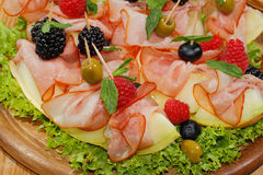 Galia melon, melon with ham, raspberries, blueberries, blackberr Royalty Free Stock Image