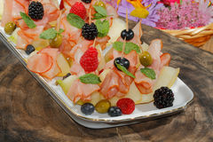 Galia melon, melon with ham, raspberries, blueberries, blackberr Stock Photography