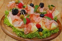 Galia melon, melon with ham, raspberries, blueberries, blackberr Royalty Free Stock Photos