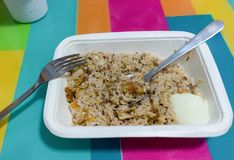 Galic fried rice and whtie boil egg in paper rectangle bowl and. Scooped spoon with fork on colorful table stock images