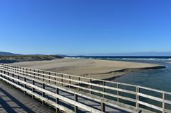 Beach with river, wooden bridge and waves. Blue sky, sunny day, Galicia, Spain. Galicia, La Coruña Province, Rias Altas, Spain. Beach with river and bridge stock images