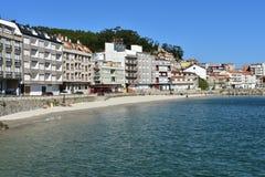 Galicia, Rias Baixas, Hiszpania Październik 2018 Ludzie sunbathing w plaży Mała nabrzeżna wioska z deptakiem i jasny wodą zdjęcia royalty free
