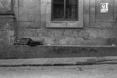 GALICIA, SPAIN – AUGUST, 1977. An unemployed man sleeps on the street under a painted social revolution during the Spanish Democratic Transition on August Royalty Free Stock Photos