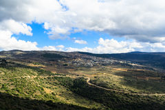 Galilee mountains landscape and small village on the hill, serpentine of roads. Galilee mountains landscape and small village on the hill, heights, blue sky with Stock Photos