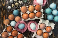 A galinha branca, azul, e amarela eggs em umas caixas de ovo da caixa e em um qua Fotos de Stock