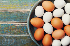 A galinha branca e marrom eggs na bacia do vintage na opinião de tampo da mesa de madeira rústica Alimento orgânico e da exploraç imagens de stock
