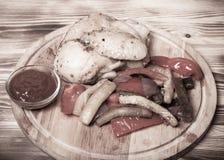 A galinha com vegetais serviu na placa de corte redonda no queimado Foto de Stock Royalty Free