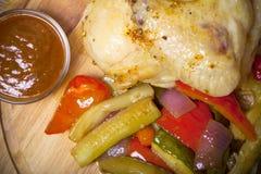 A galinha com vegetais serviu na placa de corte redonda no queimado Foto de Stock