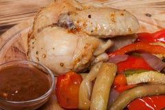 A galinha com vegetais serviu na placa de corte redonda no queimado Fotografia de Stock