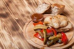 A galinha com vegetais serviu na placa de corte redonda no queimado Fotografia de Stock Royalty Free