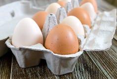 A galinha crua fresca eggs na caixa de ovo da caixa no fundo de madeira Imagem de Stock
