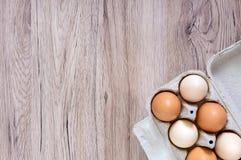 A galinha crua fresca eggs na caixa de ovo da caixa no fundo de madeira Fotografia de Stock Royalty Free