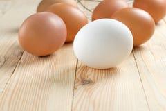 A galinha de Brown eggs com whisk na tabela de madeira foto de stock