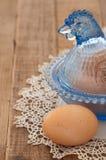 Galinha de vidro do vintage com o ovo de Brown na madeira Imagem de Stock