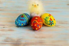 Galinha do bebê da Páscoa ao lado dos ovos no fundo de madeira azul Imagem de Stock Royalty Free